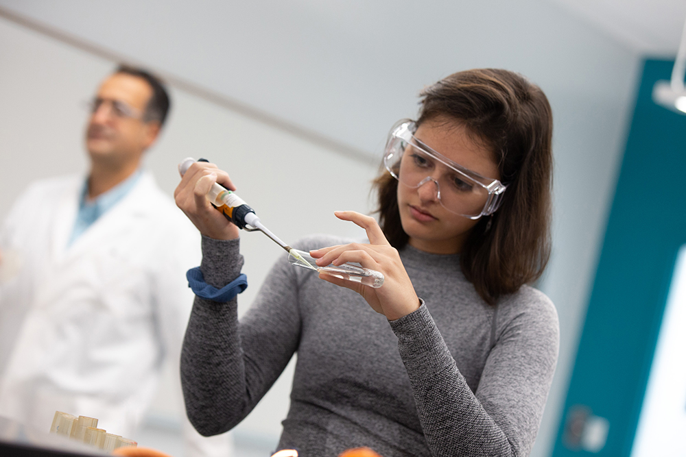Food and Biological Process Engineering student processing a test sample in the lab.