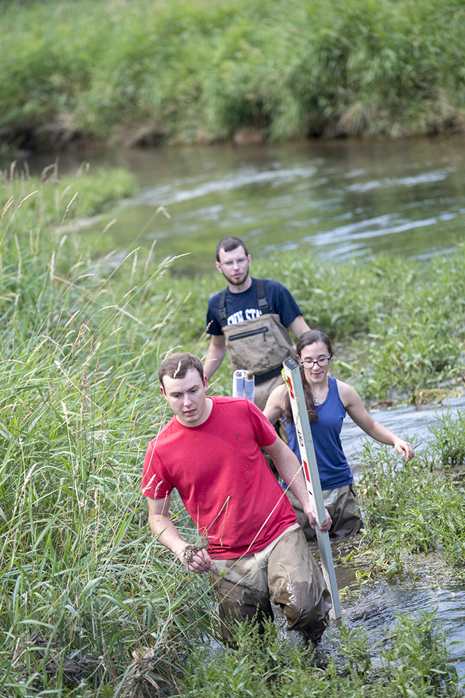 Penn State Natural Resource Engineering students crossing a river