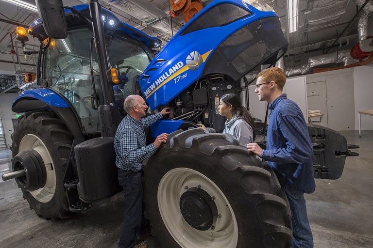 Ag systems management students and professor taking a close look at a New Holland tractor.