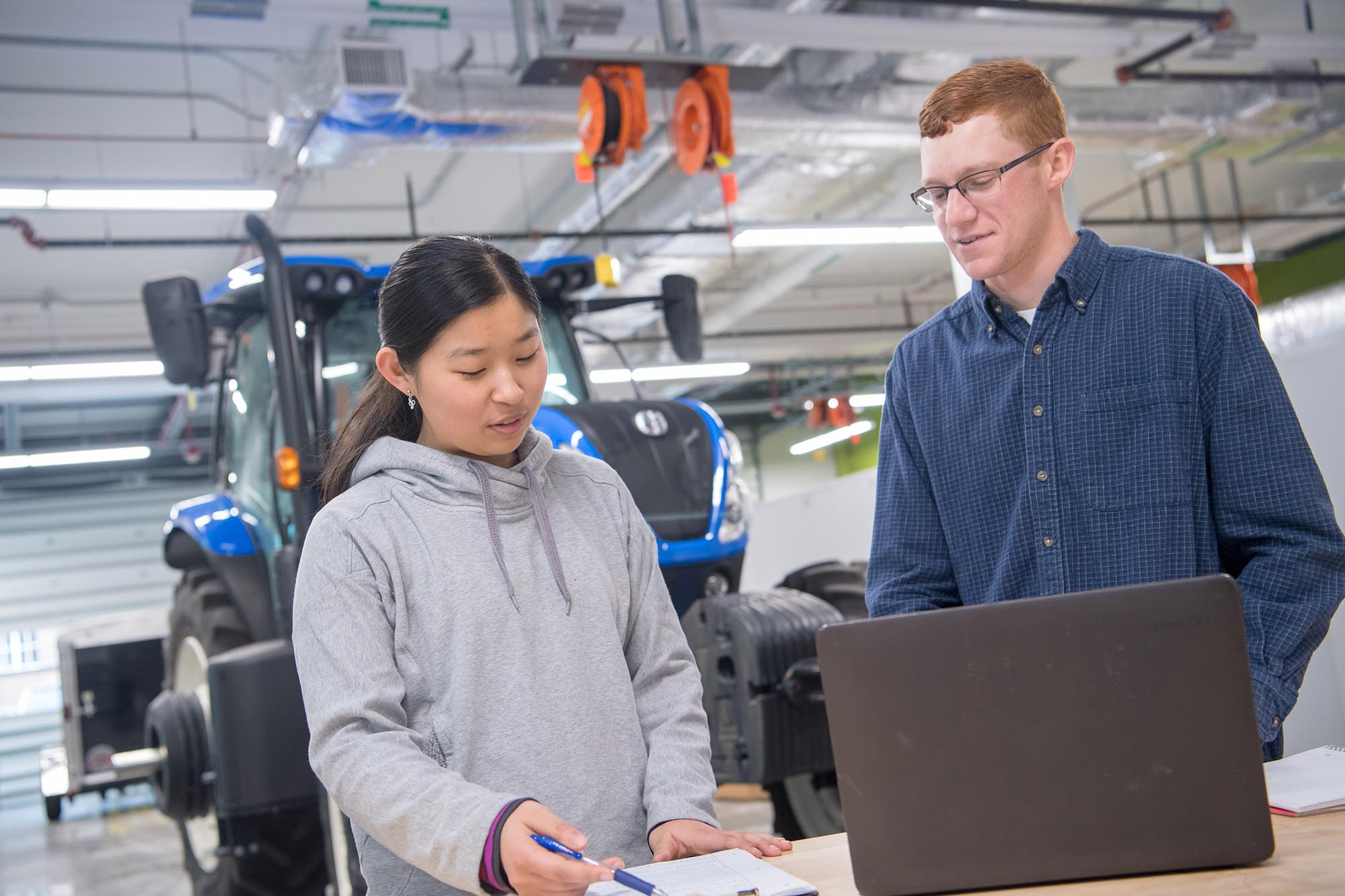 Penn State student and professor in front of agricultural machinery.