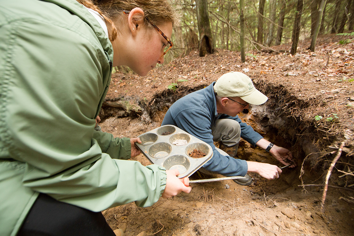 Student and professor collecting pine forest soil samples.