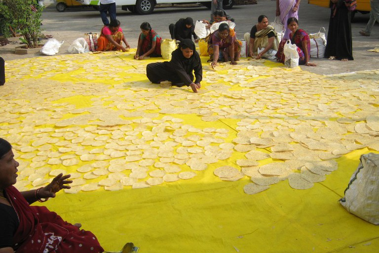 This is a picture from Lijjat Papad. Papad has to be sundried on tarps before the women sort them into stacks for packaging.