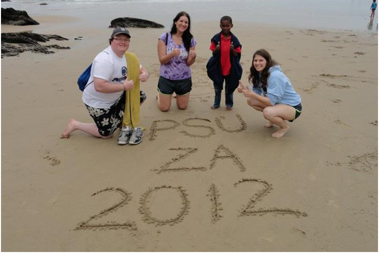 Ashley (in purple) along with two other students and a local child relaxing on the beach of the Indian ocean in South Africa about an hour away from Cape Town, South Africa.
