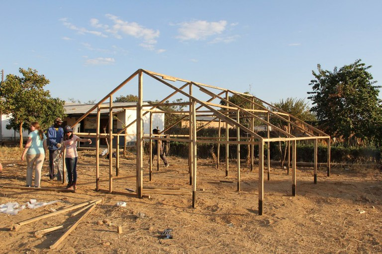 The sun begins to set as the greenhouse structure is completed in Zimba