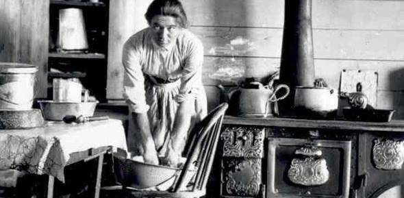 Mrs. Evelyn Cameron kneading dough in her kitchen in Montana.