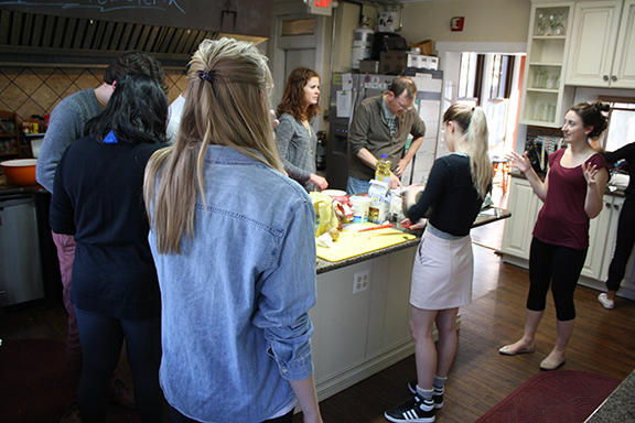 A group on people gathered around a kitchen workspace, working through a recipe together.