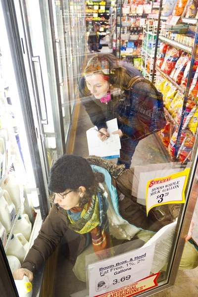 two women recording contents of grocery freezer