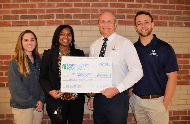 Barbara Jenkins, vice president of education and student programs for USPOULTRY and executive director of the USPOULTRY Foundation, second from left, presents a check for $10,000 to Penn State's Phillip Clauer.  Poultry Science Club Vice President Lindsey Bright is on the left; President Ethan Metzler is on the right.